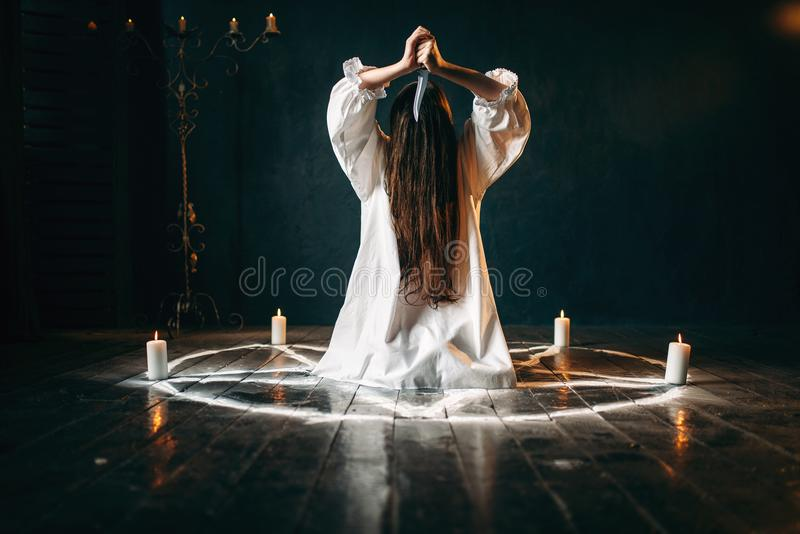 Woman with knife sitting in pentagram circle. Woman with knife in hands sitting in pentagram circle with candles. Dark magic ritual, occultism and exorcism royalty free stock photos