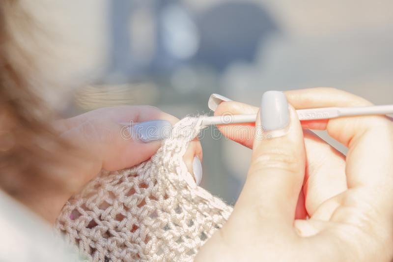 Woman knits crocheted out of wool on the street on a sunny day. Close-up. Copy space stock image