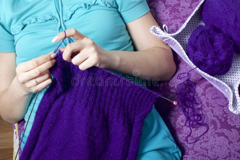 A woman knits knitting, lying in bed. A product made of string of purple. stock images
