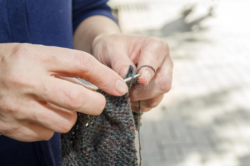 Woman knits on knitting needles out of wool on the street on a sunny day. stock photos