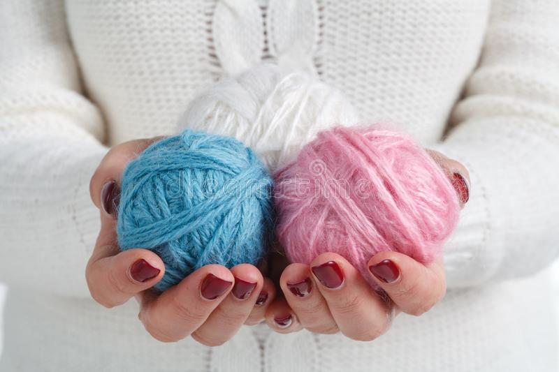 Woman in a knitted sweater holding a balls of yarn and knitting. concept of needlework royalty free stock images