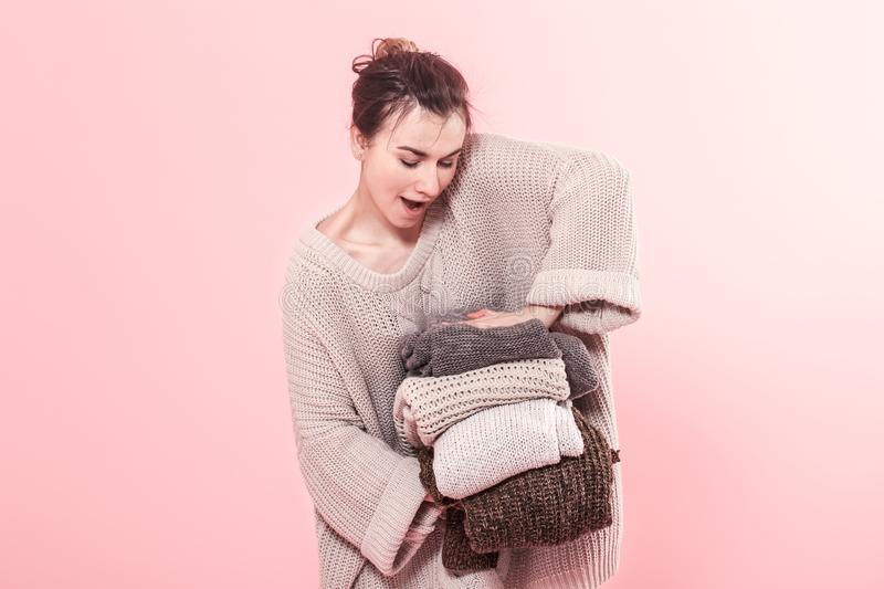 Woman in knitted sweater holds many knitted sweaters on pink background stock photos