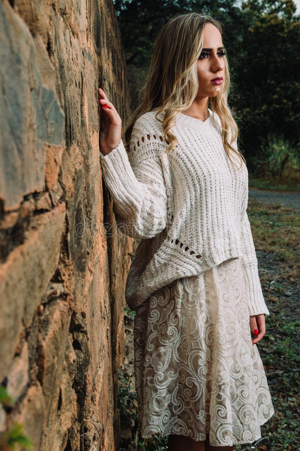 Woman in Knitted V-neck Long-sleeved Shirt and Midi Skirt Standing Beside Wall stock photography