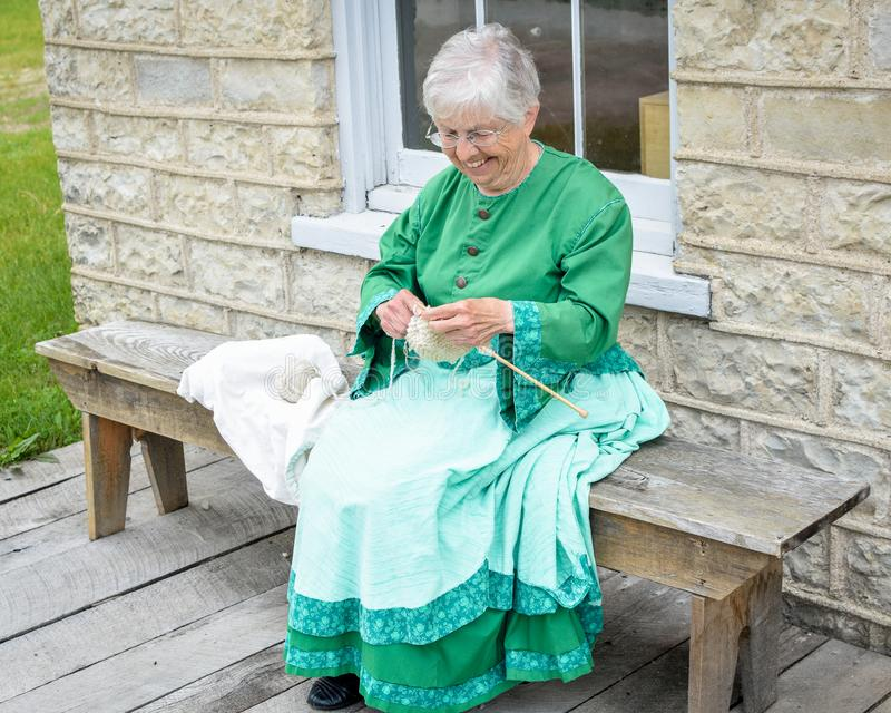Woman Knitting Outside General Store. An elderly pioneer woman reenactor, sits knitting on a bench outside of the General Store at Old World Wisconsin, a living royalty free stock images