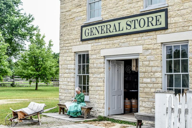 Woman Knitting Outside General Store. An elderly pioneer woman reenactor, sits knitting on a bench outside of the General Store at Old World Wisconsin, a living royalty free stock photo