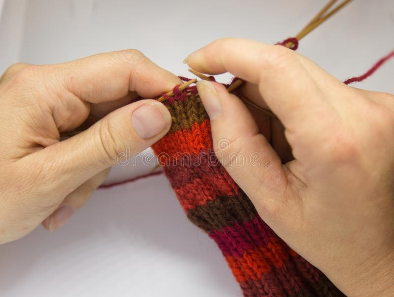 A woman knitting red woolen socks. Knitting close up on a white background. Hand crafts. Detailed view of a knitting skill royalty free stock photos