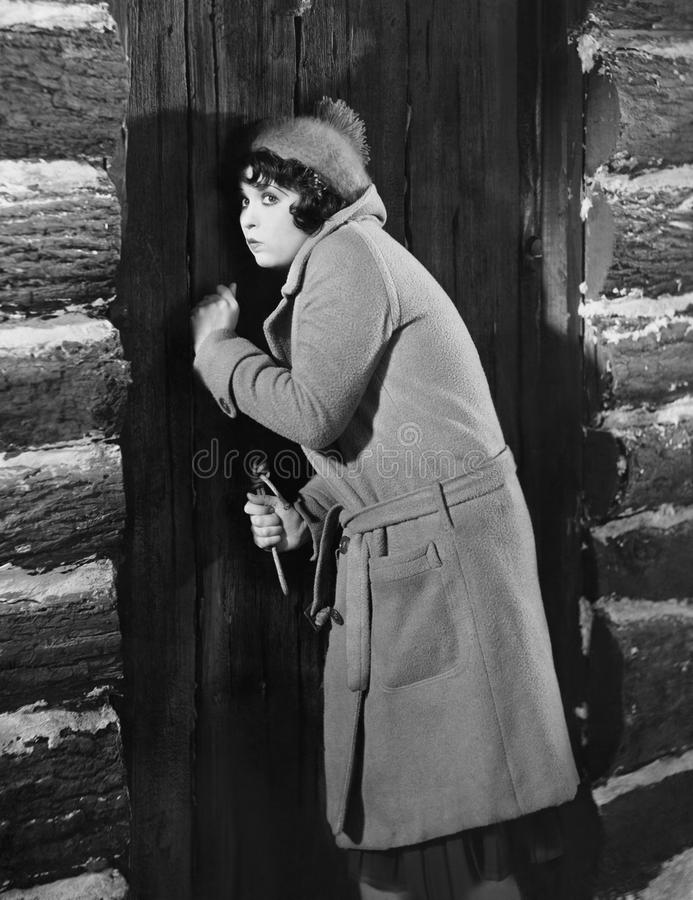 Woman knocking on cabin door. (All persons depicted are no longer living and no estate exists. Supplier grants that there will be no model release issues stock photography