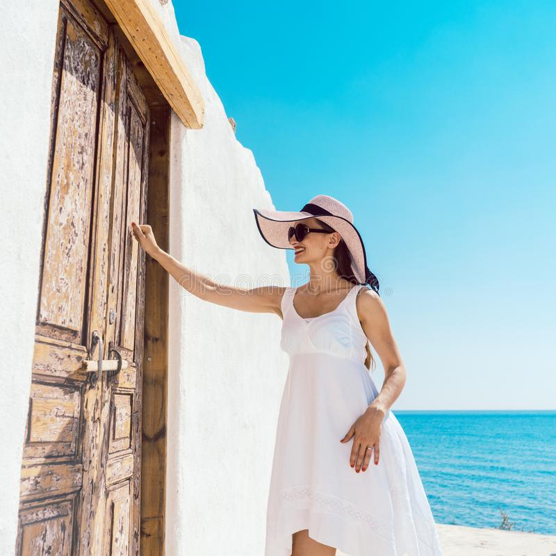 Woman knocking on the door of a beach home in Greece. The sea in the background royalty free stock photos