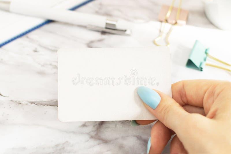 Woman& x27; la mano de s sostiene una tarjeta de visita vac?a en la oficina en la tabla de m?rmol imagenes de archivo