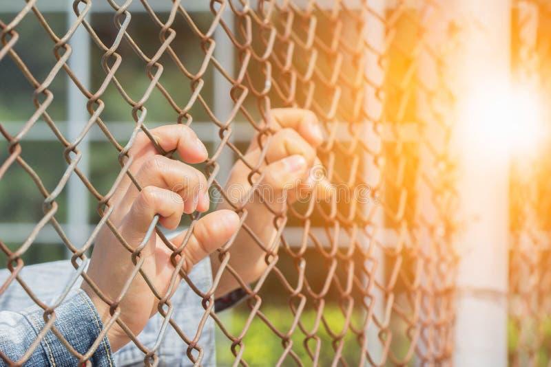 Woman& x27; la mano di s ha preso una gabbia di ferro nei posti di detenzione per attendere la libertà Fiera leggera immagine stock