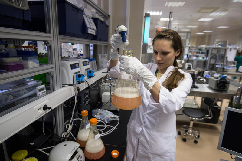 Woman laboratory assistant with flask in his hand in the biochemical laboratory stock photography