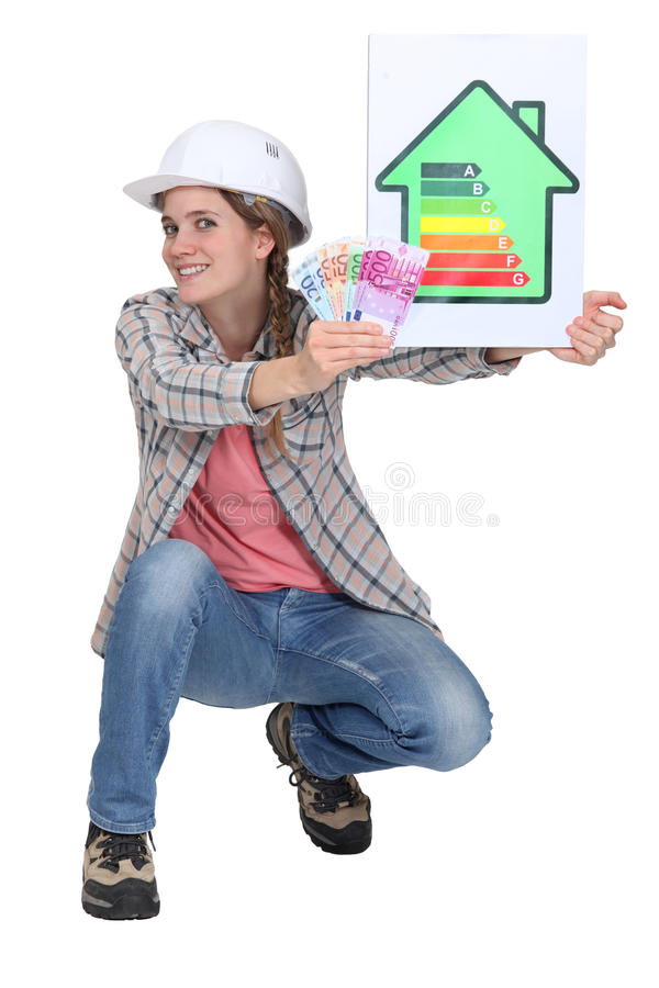 Woman laborer holding energy sign and. Woman laborer holding energy rating sign and bills stock photo