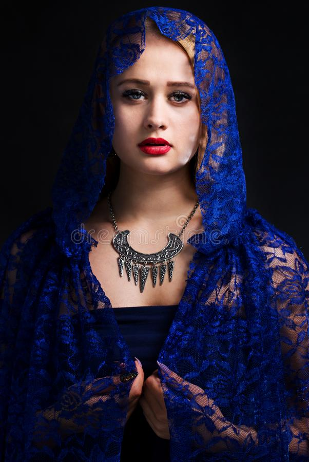 Woman in lace cape. Beautiful woman in a necklace and lace cape stock photos