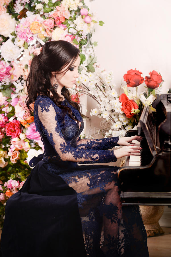 Woman in lace deep blue dress playing the piano and flowers. Retro vintage style. Woman in lace deep blue dress playing the piano and flowers. Indoor stock photos