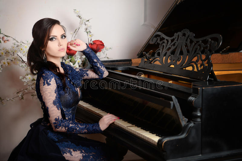 Woman in lace deep blue dress playing the piano. Retro vintage style royalty free stock image
