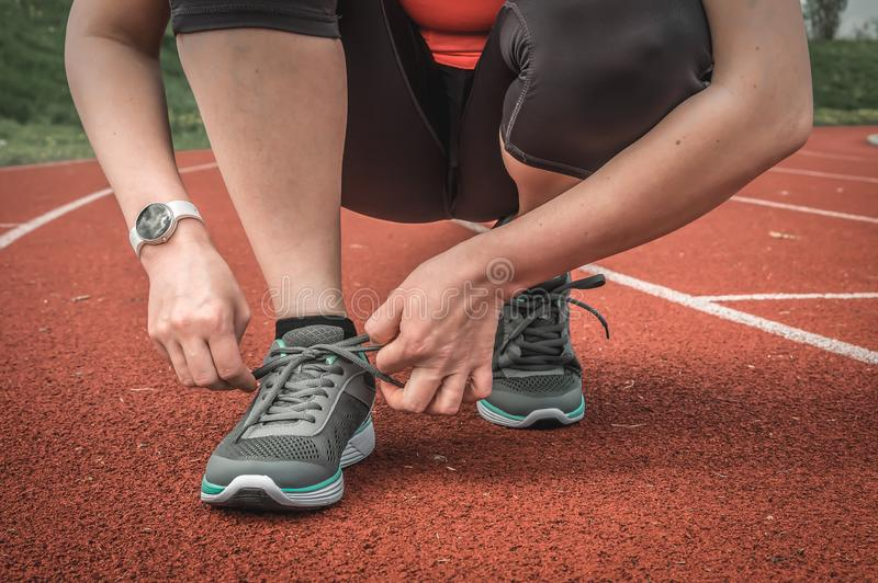 Woman is lacing her shoes on a stadium running track. Running and fitness concept stock photography
