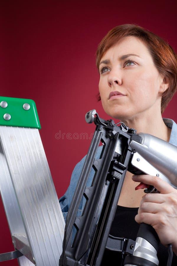 Woman on ladder holding nail gun stock photo