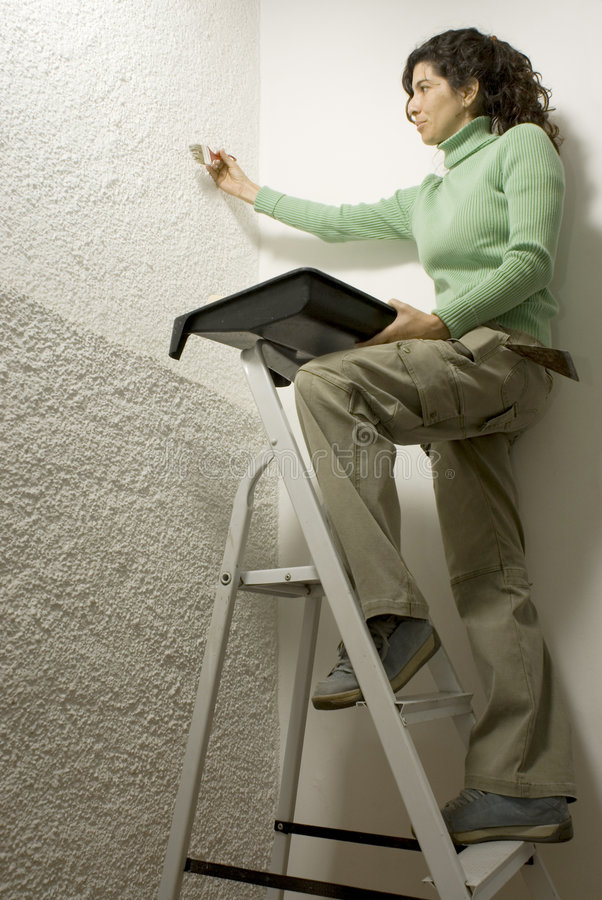 Woman on ladder - Vertical royalty free stock photo