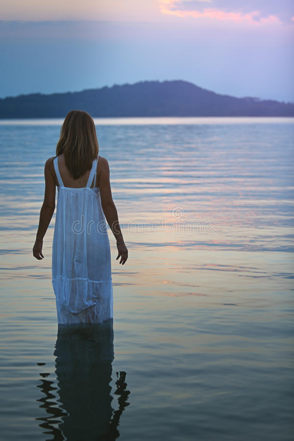 Woman in lake waters looks at soft purple sunset. Meditation and soul royalty free stock images