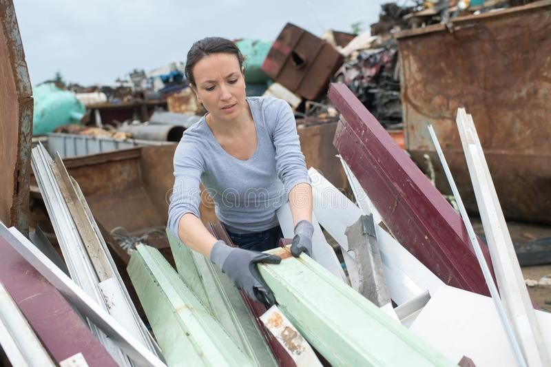 Woman landfill employee working in skip. Woman landfill employee working in a skip royalty free stock photography