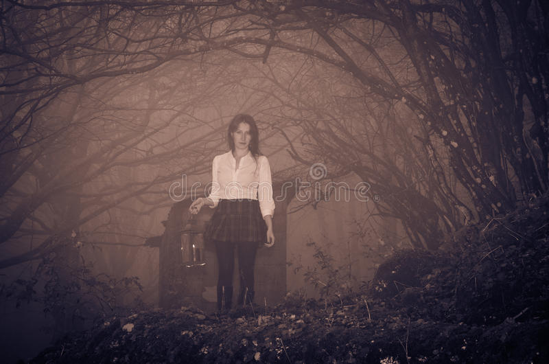 Woman with lantern in the misty forest royalty free stock image