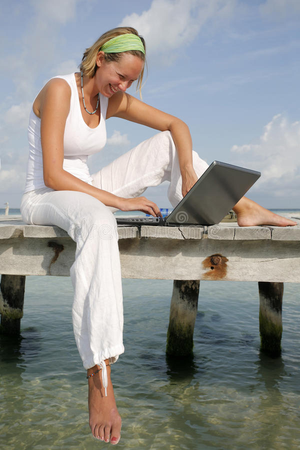 Woman and Laptop. Woman on a tropical jetty with a laptop