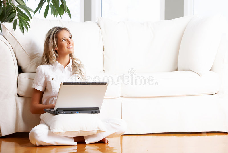 Woman with laptop. Young beautiful woman working with laptop in the new comfortable apartment