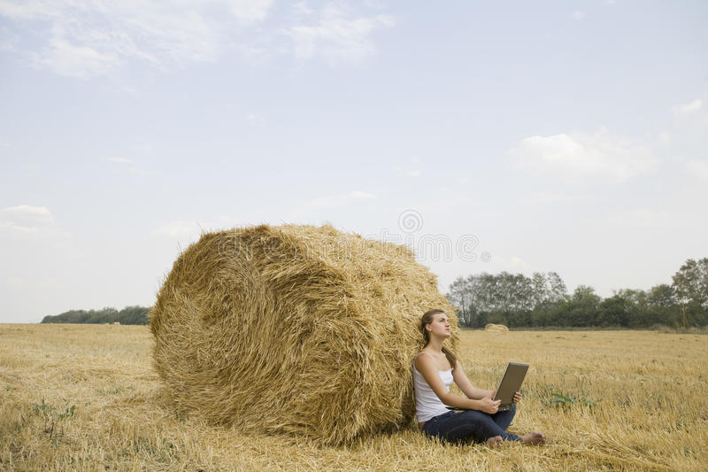 Woman With Laptop Against Hay Bale In Field. Side view of a young woman with laptop sitting against hay bale in field stock photo