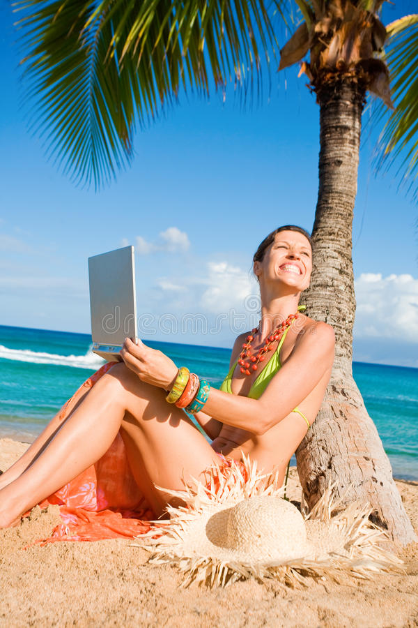 Woman with laptop beach stock image