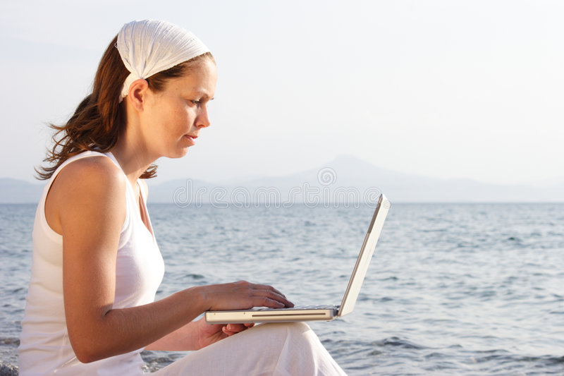 Woman with laptop on beach stock photos