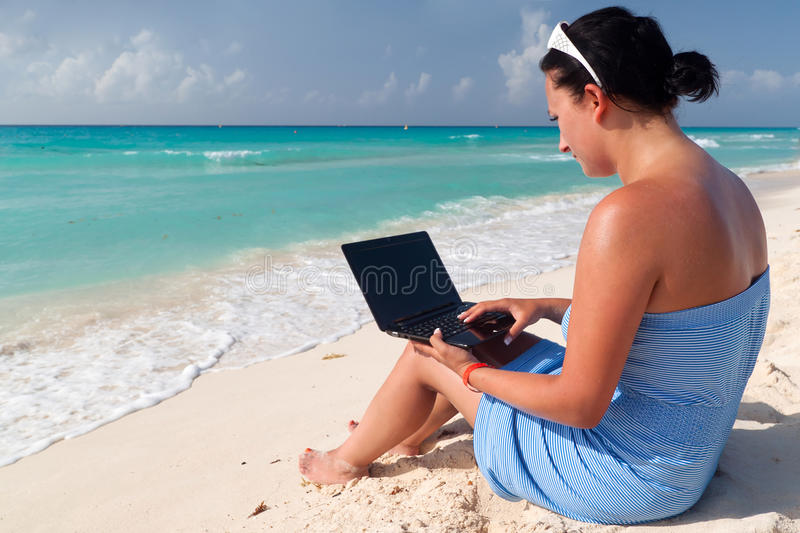 Woman with laptop at the Caribbean sea
