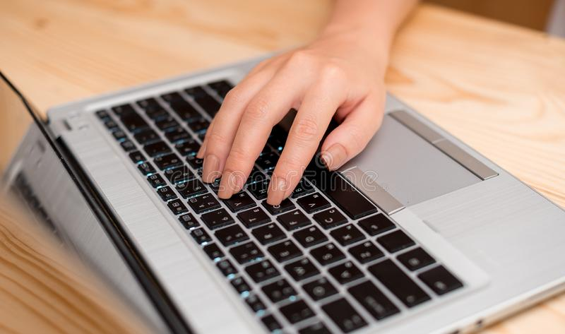 Young lady using a gray laptop computer and typing in the black keyboard with left hand in a room. Office supplies stock photography