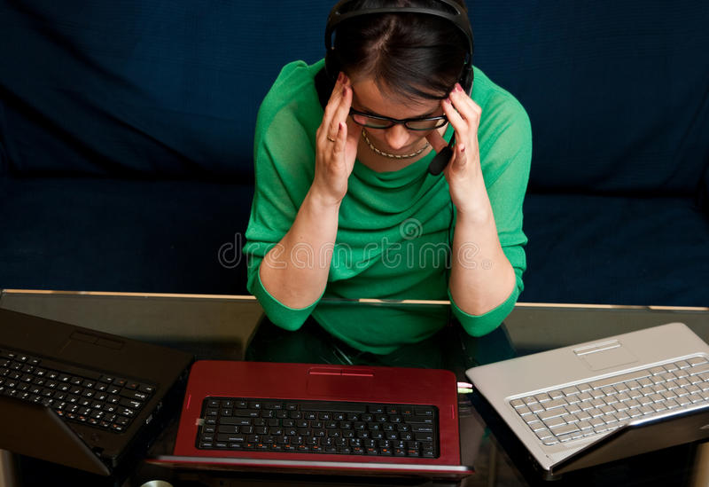 Woman with laptop computers. Multitasking concept - woman tired of working online with three laptop computers royalty free stock photo