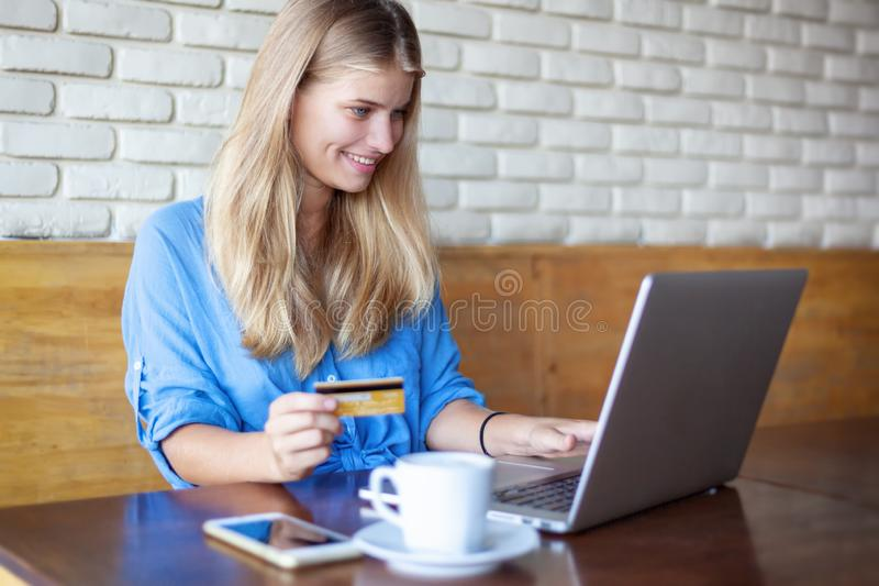 Woman with laptop and credit card in cafe . Online payment, digital banking. Young girl shopping royalty free stock photography