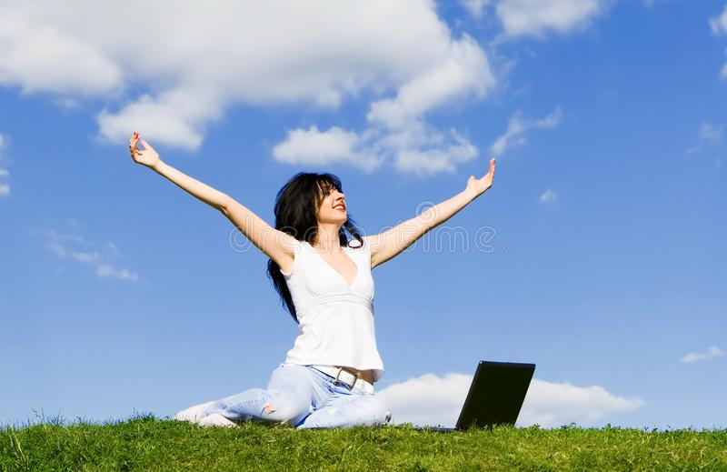Woman with laptop on the green grass royalty free stock images