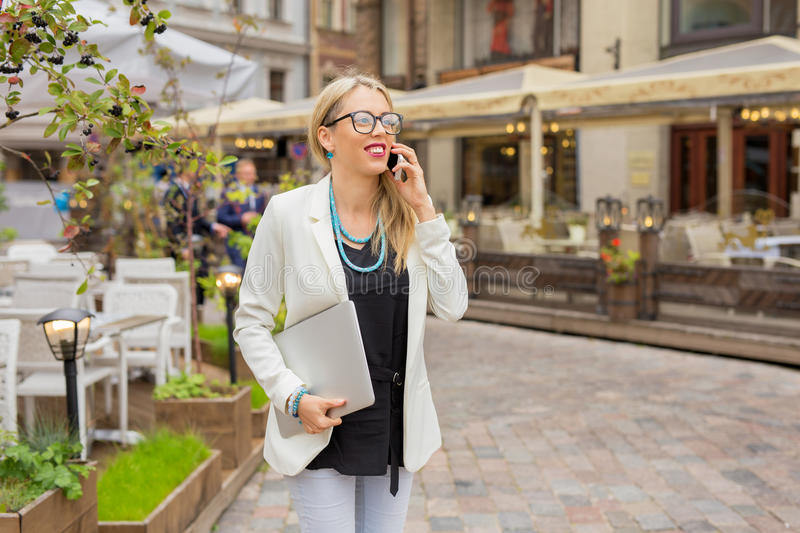 Woman with laptop in her hand talking on the phone stock image