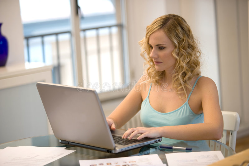 Woman at laptop at home stock photography
