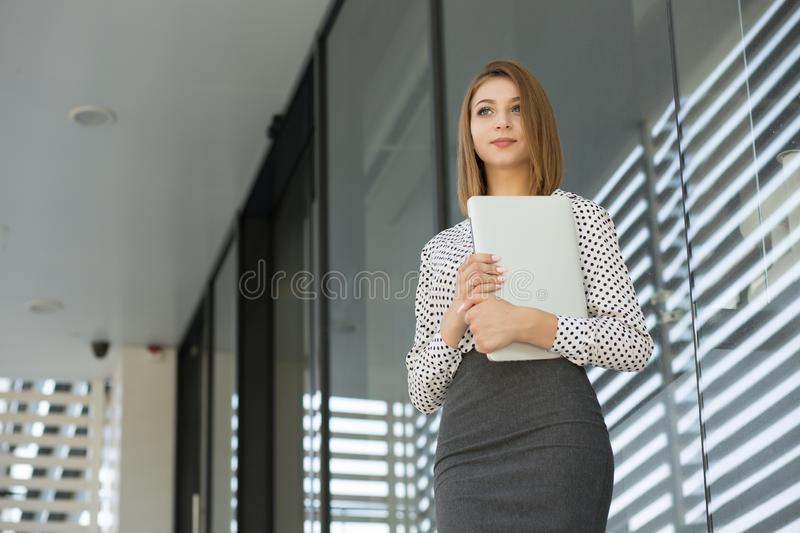 Woman with laptop looking away to the side royalty free stock image