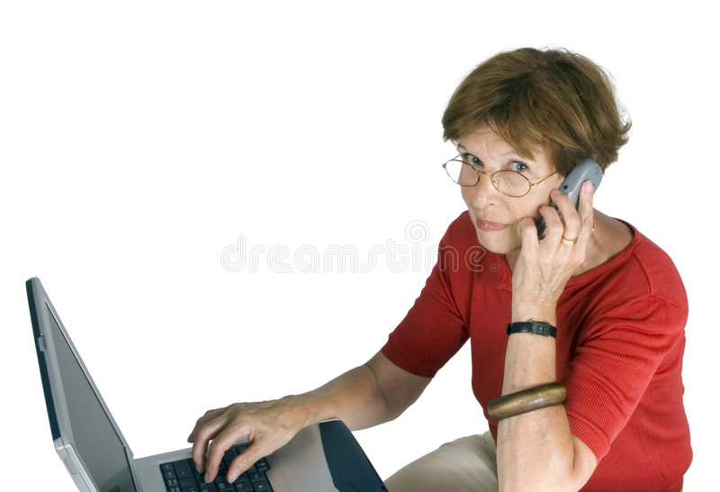 Woman with laptop and mobile. Middle aged woman with open laptop and mobile telephone, white studio background stock photography