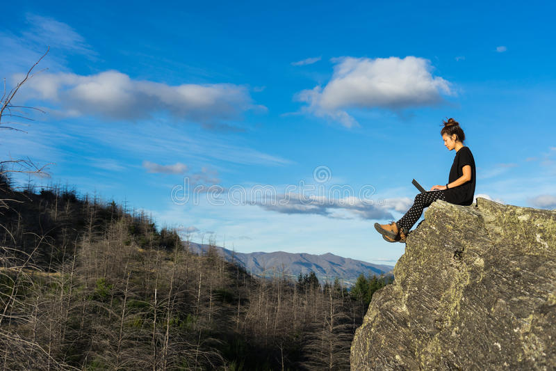 Woman with laptop on the mountain royalty free stock photos