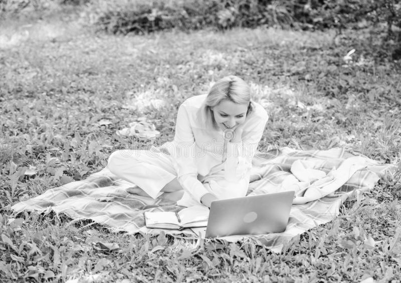 Woman with laptop or notebook sit on rug green grass meadow. Business lady freelancer work outdoors. Business picnic. Concept. Steps to start freelancing royalty free stock images