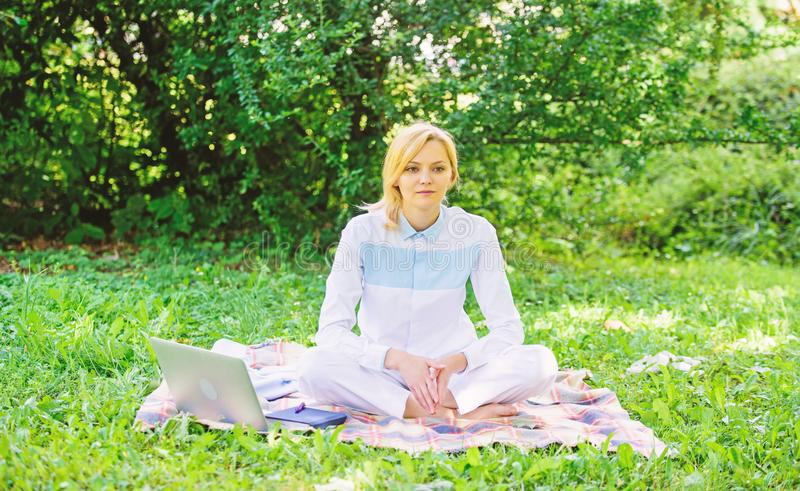 Woman with laptop or notebook sit on rug green grass meadow. Business picnic concept. Steps to start freelancing royalty free stock photography