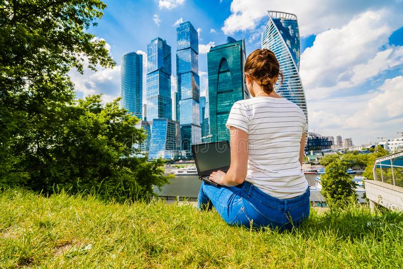 Woman with laptop notebook sitting on the grass. She is in blue jeans and a white t-shirt. Landscape with skyscrapers. Back view of Girl with laptop notebook stock photo