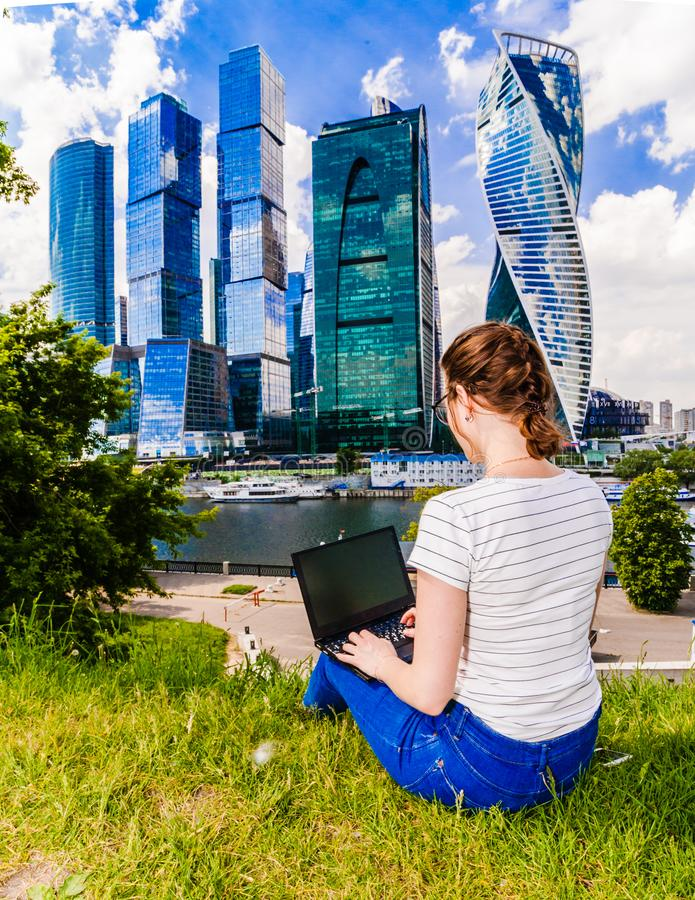 Woman with laptop notebook sitting on the grass. She is in blue jeans and a white t-shirt. Landscape with skyscrapers. Back view of Girl with laptop notebook stock images