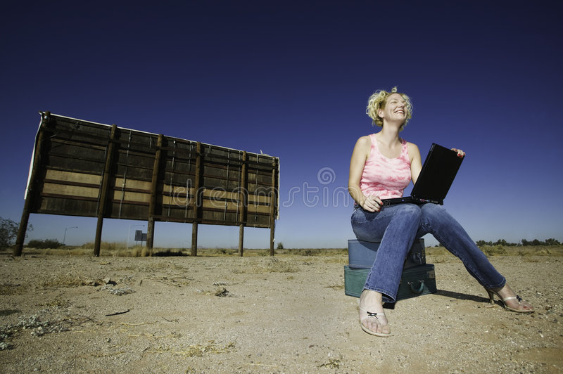Woman with a laptop ourdoors. Woman with a laptop computer outside in front of an old bilboard stock photo