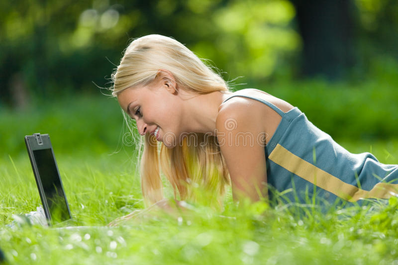 Woman with laptop, outdoors. Young woman with laptop, outdoors royalty free stock photo