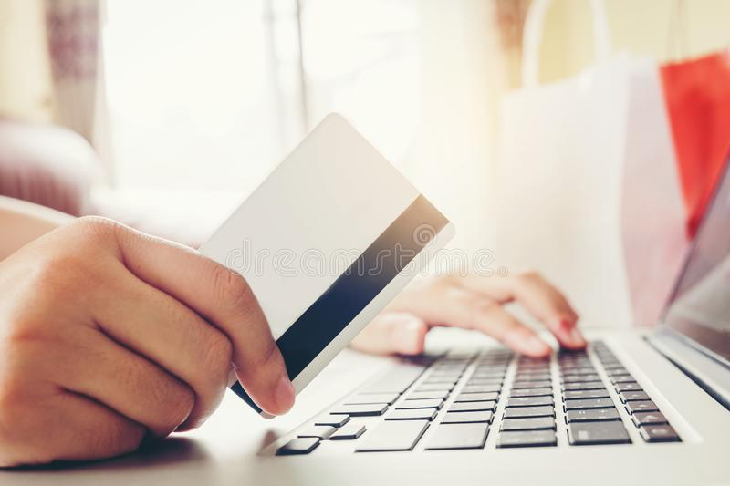 Woman with laptop shopping online with debit card in cafe.  royalty free stock photography