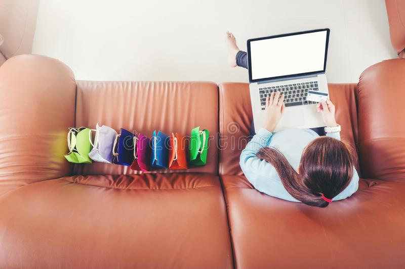 Woman with laptop shopping online with debit card on sofa in home.  royalty free stock photography