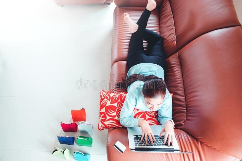 Woman with laptop shopping online with debit card on sofa in home.  stock photo
