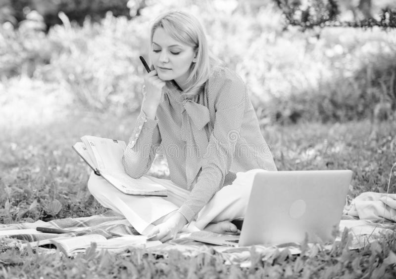 Woman with laptop sit grass meadow. Business lady freelance work outdoors. Freelance career concept. Guide starting stock photo